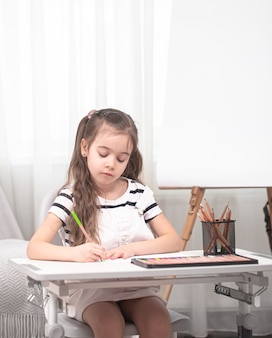 Cute girl schoolgirl sitting at the table and doing homework homeschooling.