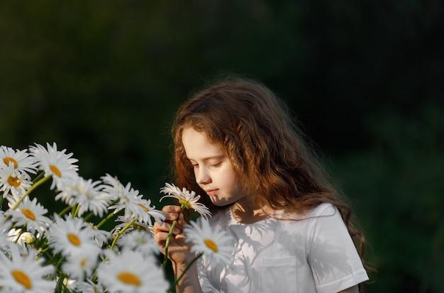 Милая девушка обстреливает цветок ромашки.