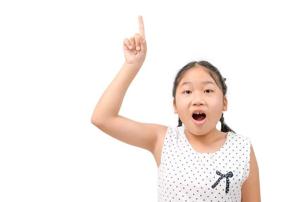 かわいい女の子はショックを受け、白い背景、コピースペースに隔離された彼女の指を上向きに向けます