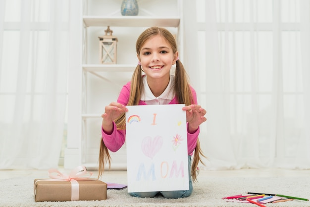 Cute girl showing drawing with i love mom inscription
