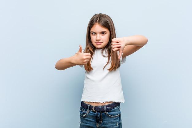 Милая девушка показывает палец вверх и пальцы вниз, трудно выбрать концепцию