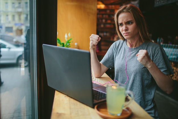 A cute girl sits in a cafe and works at the computer she is angry
