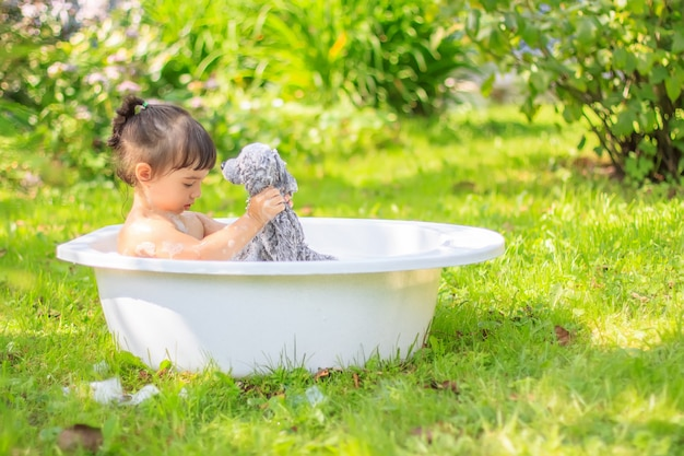 Cute girl sitting in the bath with a plush toy in a green summer garden, on a sunny day