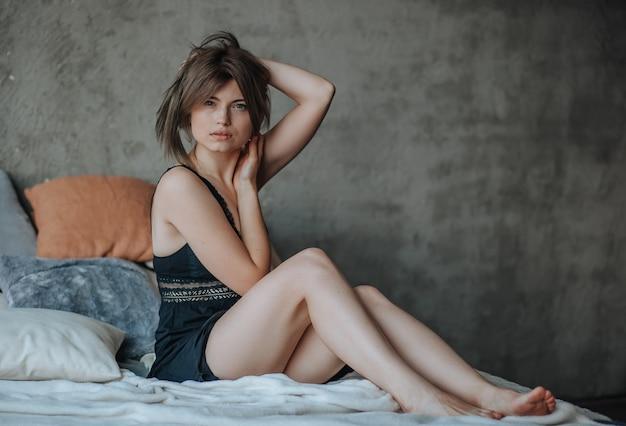 Cute girl sitting on bed in morning in black lingerie