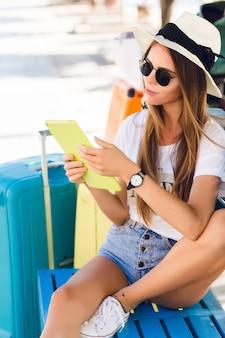 Ragazza carina che si siede su una panchina blu e gioca su un tablet in custodia gialla.
