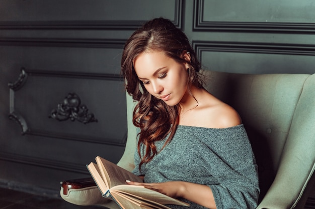 Cute girl sitting in a chair and reading a book in the office