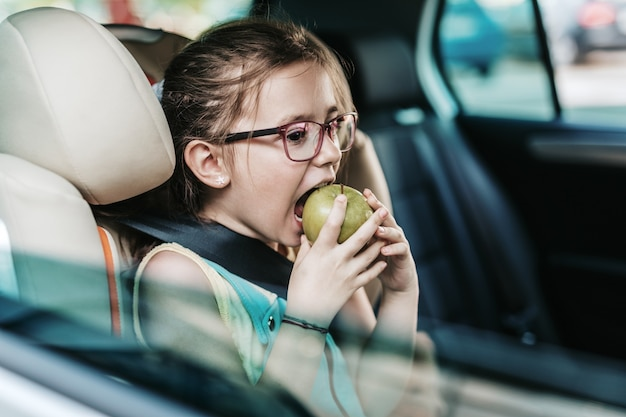 안전 어린이 카시트에 차에 앉아 귀여운 소녀.