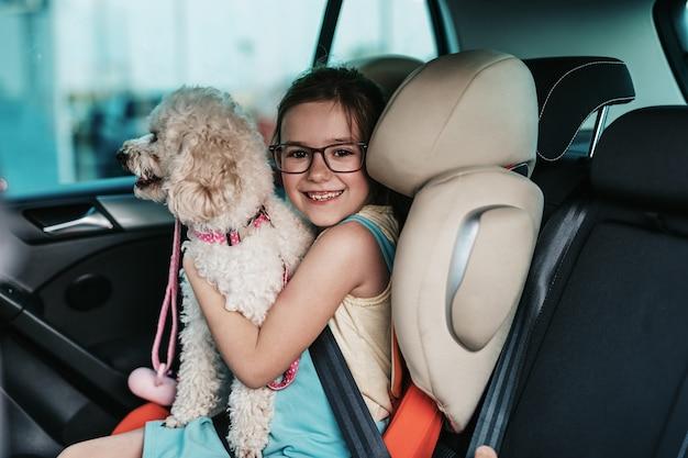 안전 어린이 카시트에 강아지와 함께 차에 앉아 귀여운 소녀.
