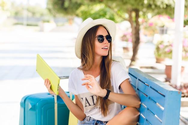 青いベンチに座って、黄色のケースでタブレットで遊ぶかわいい女の子。