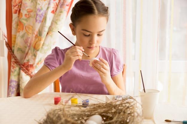 Милая девушка сидит на кухне и рисует пасхальное яйцо