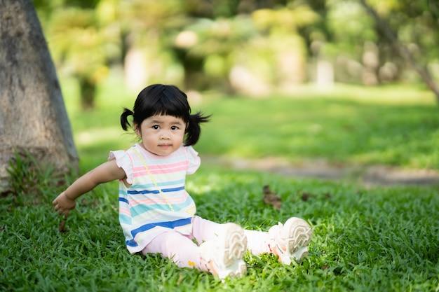 Милая девушка сидит на лужайке в саду