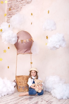 Cute girl sitting on wall of a balloon, stars and clouds and holding a teddy bear. little girl is dreaming. girl plays in the children's room with a toy. child room decor. baby and stuffed toy