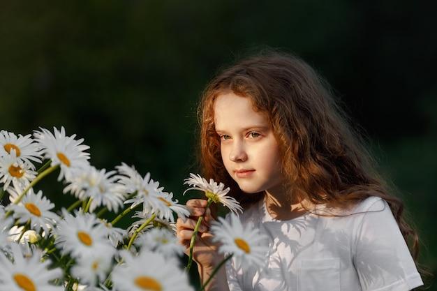 Милая девушка, пахнущая цветами ромашки