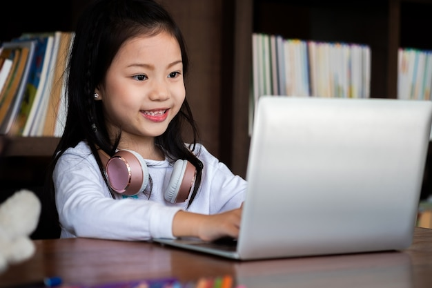 Cute girl smile sit and playing laptop computer in the library
