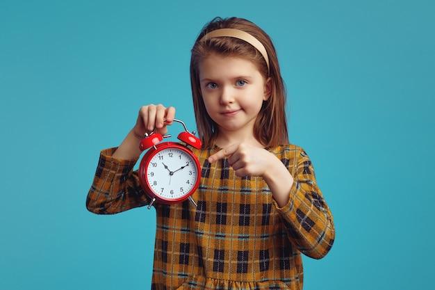 Милая девушка улыбается и указывает на классический красный будильник на желтом фоне