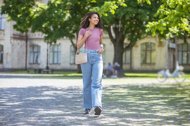 Милашка. улыбающаяся милая мулатта в джинсах и розовой футболке в парке Premium Фотографии