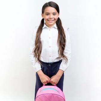 Милая девушка улыбается с рюкзаком