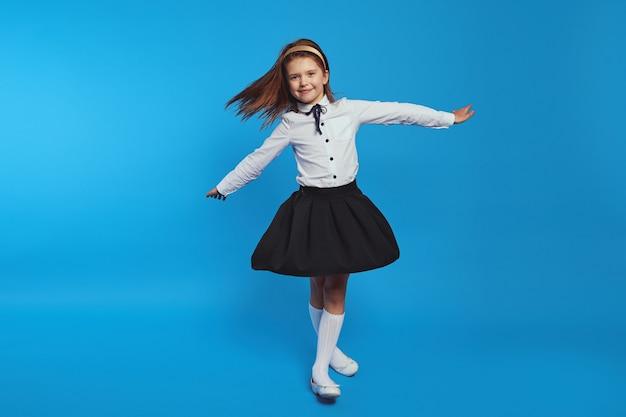 Милая девушка быстро вращается в школьной форме, от чего оно вспыхивает