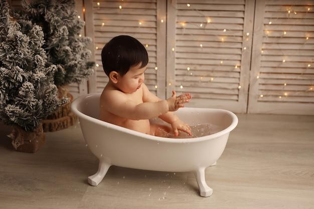 화환이 있는 크리스마스 트리 배경에 욕조에서 튀는 귀여운 소녀