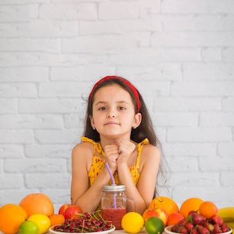 Cute girl standing against white wall with colorful fruits