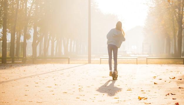 もやの中でスクーターに横に立っているかわいい女の子