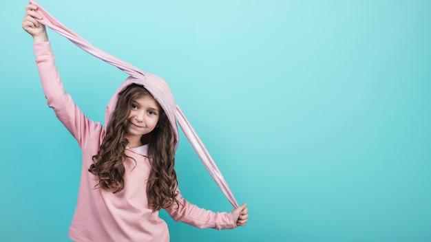 Cute girl standing in hood with bunny ears