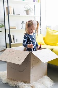 Симпатичная девушка, стоящая в картонной коробке и украшая ее фломастером Бесплатные Фотографии