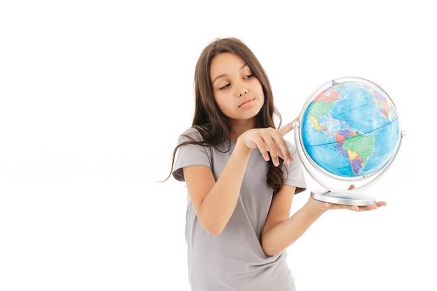 Милая девушка стоя изолированно держа глобус.