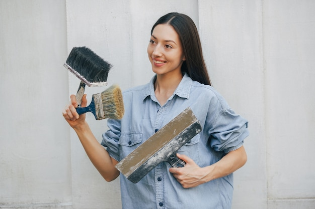 Cute girl standing near wall with repair tools