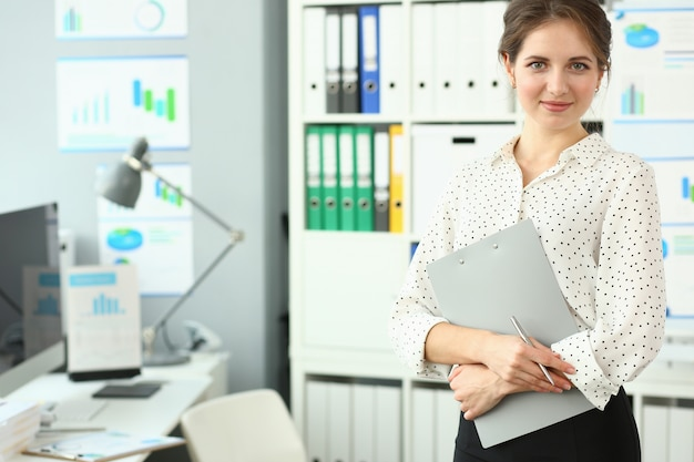 Cute girl standing near workplace