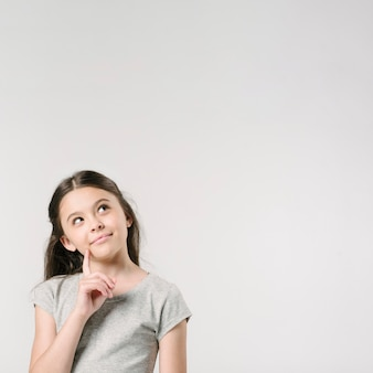 Cute girl standing in studio dreaming