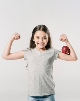 Cute girl standing with apple on bicep in studio