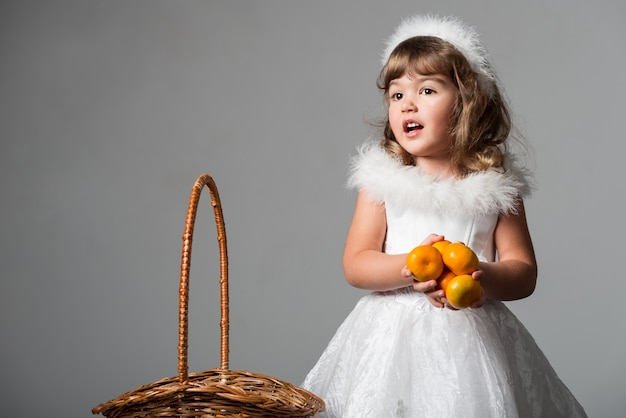 Cute girl standing with basket and holding citrus fruits
