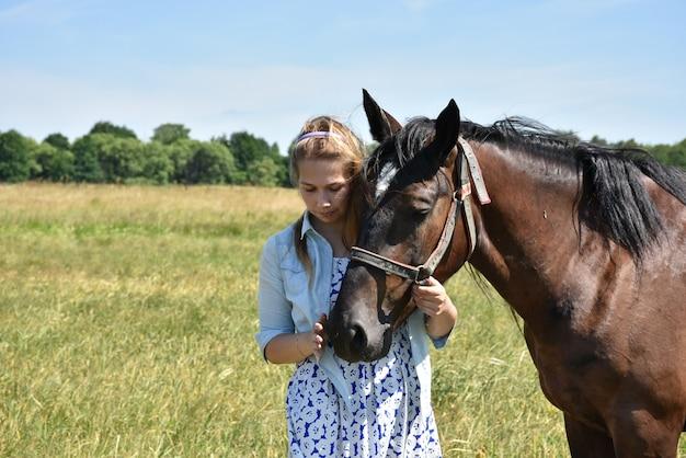 かわいい女の子は、フィールドの上に茶色の馬と一緒に立っています。