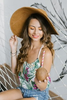 Cute girl in a straw hat on vacation, resting and holding a coconut with a straw