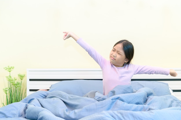 Cute girl stretching in bed after waking up,