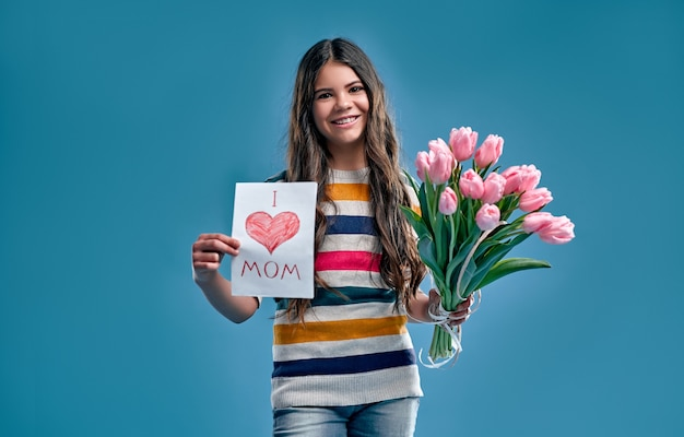 Cute girl in a striped multi-colored sweater holds a bouquet of tulip flowers and a card for her mom isolated on a blue.