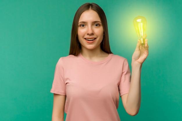 귀여운 여자 학생은 그녀의 손에 램프를 보유하고 있습니다. 아이디어 또는 창의적인 통찰력의 개념.