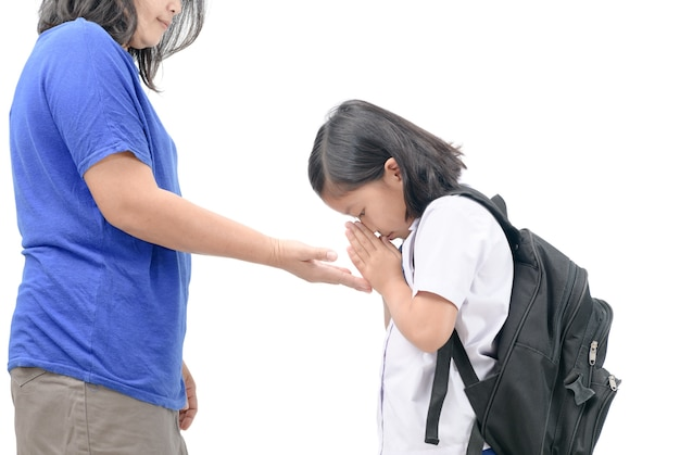 Cute girl student pay respect or sawasdee to her mother