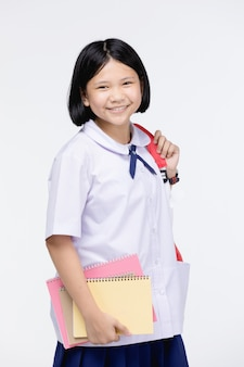 Cute girl in student's uniform with stationery on gray