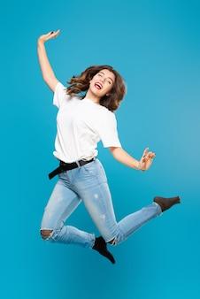青い上の彼女の顔に笑顔で手を振ってジャンプするかわいい女の子の学生のティーンエイジャー