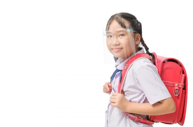 顔のシールドを身に着けているかわいい女子学生と分離された学校に行くためにランドセルを運ぶ