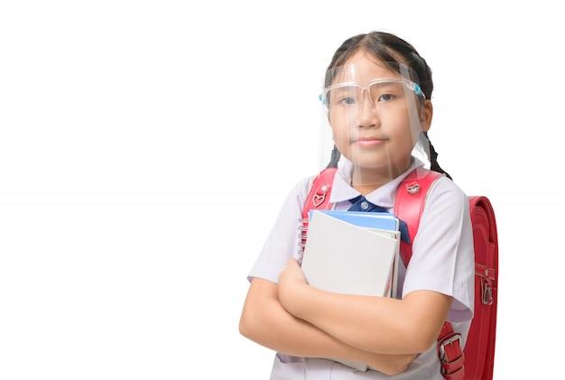 本を持って顔シールドを身に着けているかわいい女子学生とランドセルを運ぶ