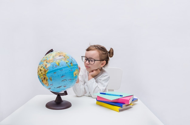 Cute girl student with glasses in a white jacket sits at a table and looks at the globe of the world on a white isolated