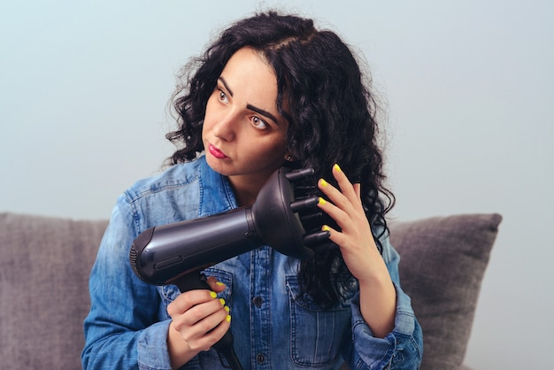 Cute girl styling her curly hair with hairdryer with special diffuser nozzle