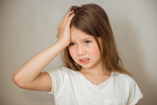 Милая девушка страдает от головной боли на сером фоне
