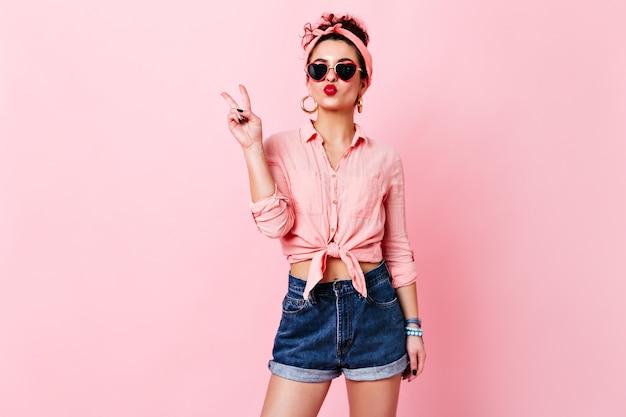 Ragazza carina in occhiali da sole a forma di cuore soffia bacio. donna in archetto, camicetta e shorts in denim che mostra il segno di pace.