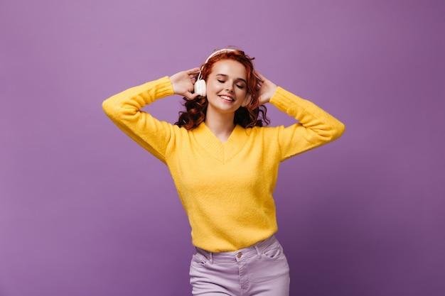 La ragazza carina in maglione ascolta musica in cuffie bianche e balla sul muro viola
