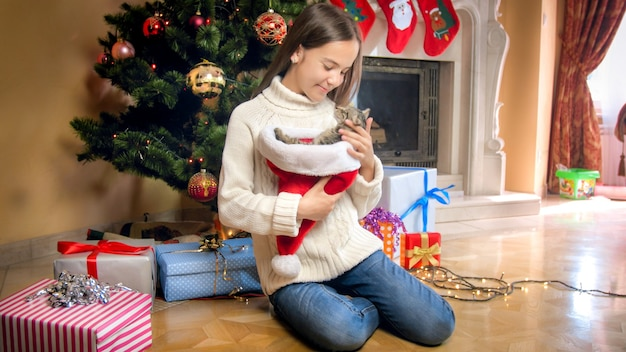 Cute girl in sweater posing with grey kitten under christmas tree