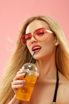 Cute girl in swimsuit posing at studio and drinking orange juice. summer portrait caucasian teenager on a pink background.